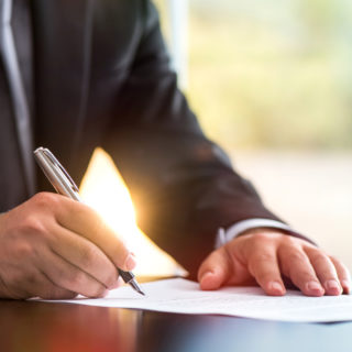 Corporate Man Signing a Document - Banner Image for Outsourcing your Certificate of Insurance Services Blog